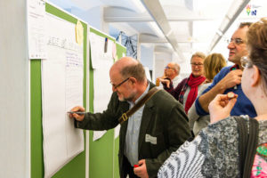 """Workshop-Teilnehmer steht vor Pinnwand und notiert etwas an eines der Plakate zu den Handlungsfeldern """"Ziele und Maßnahmen für Inklusion"""""""