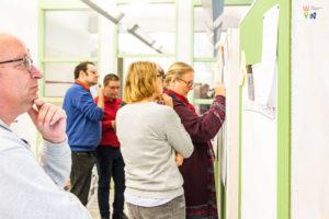 """Workshop-Teilnehmende stehen vor Pinnwänden und notieren etwas an eines der Plakate zu den Handlungsfeldern """"Ziele und Maßnahmen für Inklusion"""""""